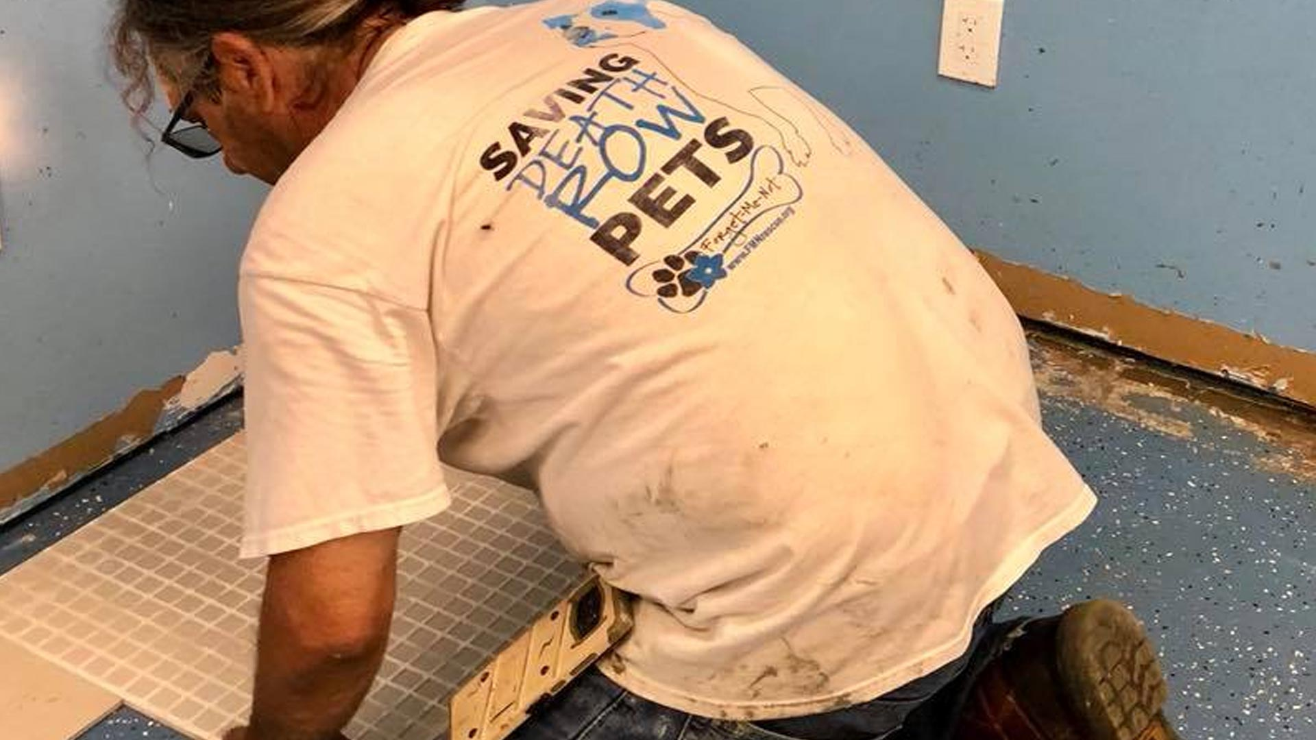 A volunteer laying tile at a new shelter in Bradenton for our large breed dogs that are available for adoption.